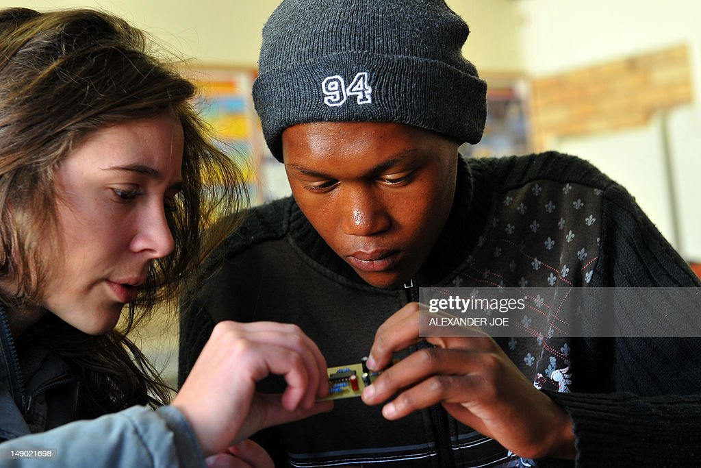 STORY by Justine Gerardy A picture taken on July 7, 2012 shows Lise Du Buisson (L), a final year Science student at Stellenboch University, explaining to Edward Bostander, a 16 year old student at Carnavon High School, how to make a radio, as part of the outreach project by The Square Kilometre Array (SKA) to groom South African future scientists. The sleepy South African town of Carnarvon has more churches than ATMs, but science is breathing new life into the far-flung farming centre. The former 19th century mission station is the closest town to the science and astronomy hub that is forming in the arid central Karoo where the Square Kilometre Array (SKA) mega-telescope will be built.