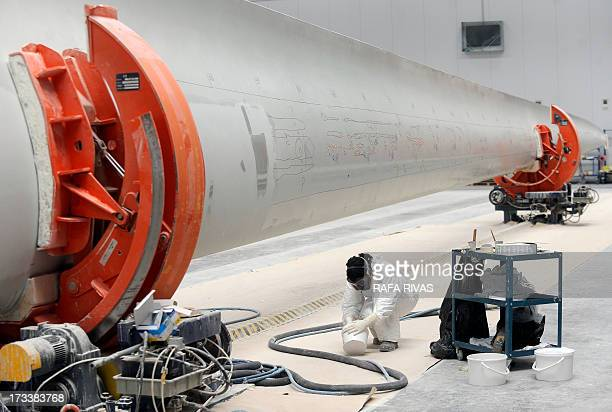 STORY by Katell ABIVEN A picture taken on July 8 2013 shows a woman working on a wind turbine at a manufacturing plant of Gamesa company in the...