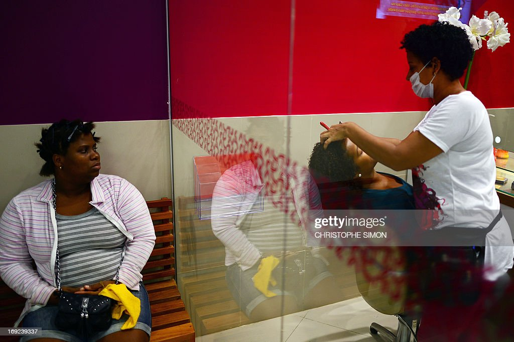 STORY by LAURA BONILLA A customer waits for her turn at a hairdresser's specialized in curling hair --Afro-style hairdressing-- in Rio de Janeiro, Brazil on May 7, 2013. AFP PHOTO/CHRISTOPHE SIMON