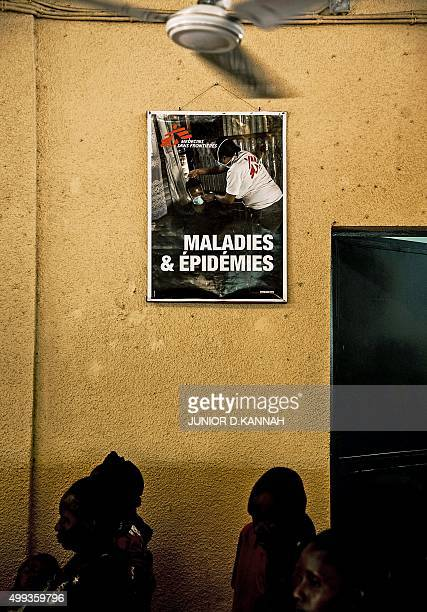 STORY by Marc JOURDIER People stand under a poster at the MSF HIV centre in Lingala on November 30 2015 The MSF AIDS project in Democratic Republic...