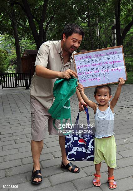 WITH 'OLY2008CHNRIGHTSPROTEST' by Marianne Barriaux Hai Mingyu hands a placard to his son to hold up in protest at a Beijing park on August 9 2008 in...