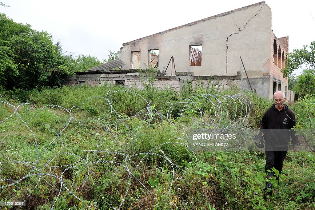 STORY by Max DELANY Amiran Gugutishvili, 67, walks near four-foot (1.2-metre) high coils of razor wire that divide the Russian-backed breakaway territory from Georgian-controlled land in village of Gugutiandkari in Georgia on July 25, 2013. On the night of August 7-8, 2008, Georgia's pro-Western President Mikhail Saakashvili launched an offensive to reclaim breakaway region South Ossetia only to see Russian forces sweep into Georgia. The 2008 war between Georgia and Russia over the separatist region of South Ossetia may have only lasted five days.