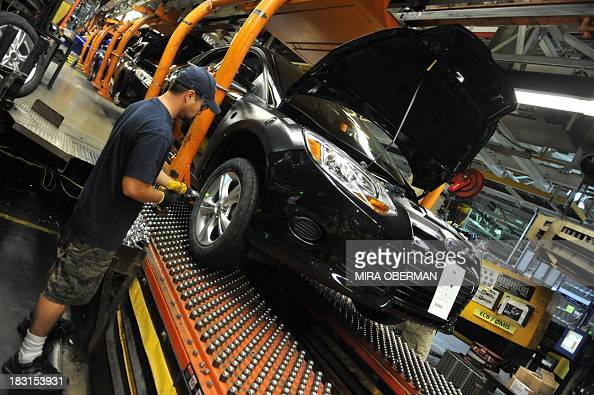 STORY by Mira OBERMAN USautohistorycompanyFord An auto worker tightens bolts on the wheel of a Focus at Ford's Michigan Assembly Plant on October 1...