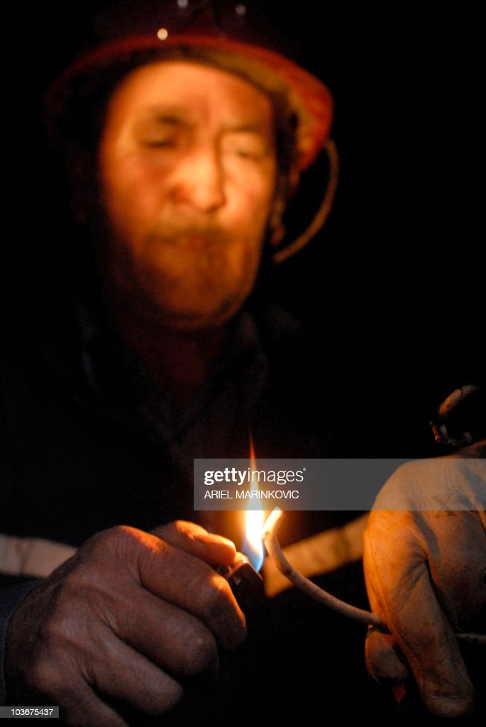 STORY by Moises Avila Roldan Emilio Tapia lights the safety fuse of a dinamite cartridge in a shaft of the San Javier mine, near Copiapo (800 kms al norte ... - by-moises-avila-roldan-emilio-tapia-lights-the-safety-fuse-of-a-in-picture-id103675437