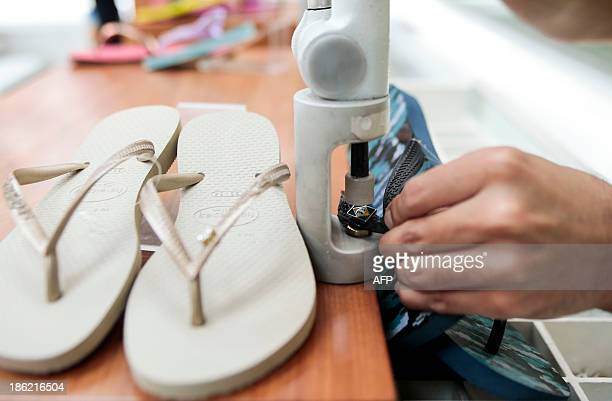 STORY by Natalia Ramos A Brazilian flag shoe decoration is set in a famous Havaianas flipflop at a stand in Sao Paulo Brazil on October 29 2013 AFP...