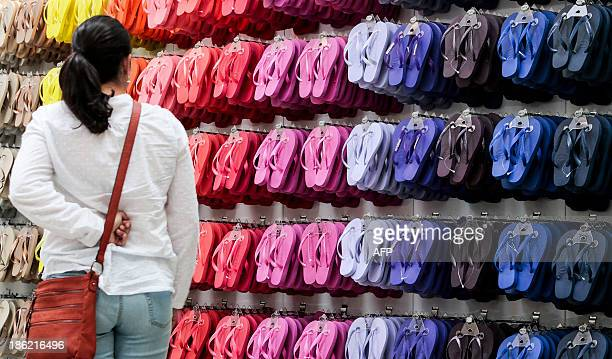 STORY by Natalia Ramos A woman looks at the Brazilian famous Havaianas flipflops at a store in Sao Paulo Brazil on October 29 2013 AFP PHOTO / Miguel...
