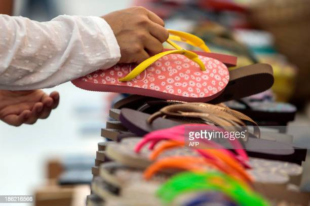 STORY by Natalia Ramos A woman picks a pais of the Brazilian famous Havaianas flipflops in Sao Paulo Brazil on October 29 2013 AFP PHOTO / Miguel...