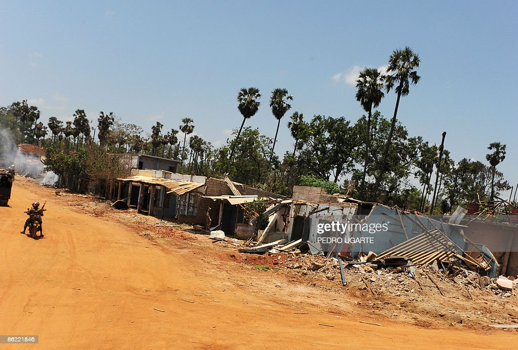 By Nicolas Revise This picture taken on April 24 2009 shows Sri Lankan soldiers riding a motorcycle past a destroyed village along on the road from...