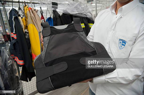 STORY by Nina Negroni An employee shows a bulletproof vest which is part of the armoured clothing line produced at the factory of Colombian...