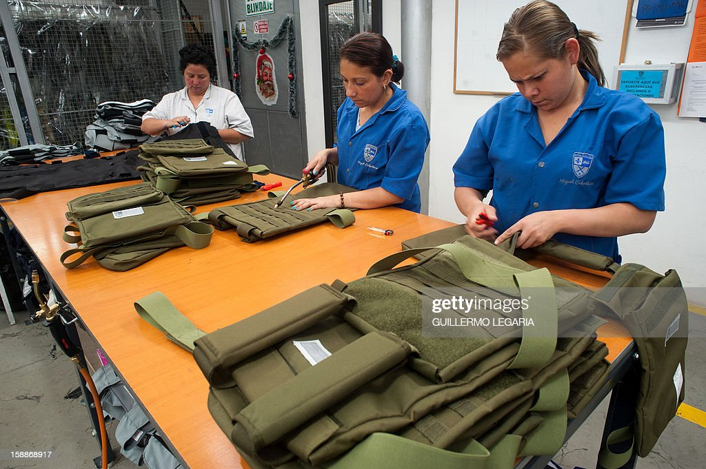 STORY by Nina Negroni Employees give the finishing touches to vests and other armoured clothing at the factory of Colombian businessman Miguel Caballero on the outskirts of Bogota, on December 28, 2012. For 20 years, Miguel Caballero has designed and produced body armour for officers and personalities around the world, but is now also working in a line bullet-and-stab-proof wear for children to sell in the US. On the heels of the deadly shooting tragedy in Connecticut, US, in which 20 children and six women were killed, parents' anxiety is driving a surge in sales of bullet-proof backpacks, in the hope the armored bags can give their kids a safety edge. AFP PHOTO/Guillermo Legaria