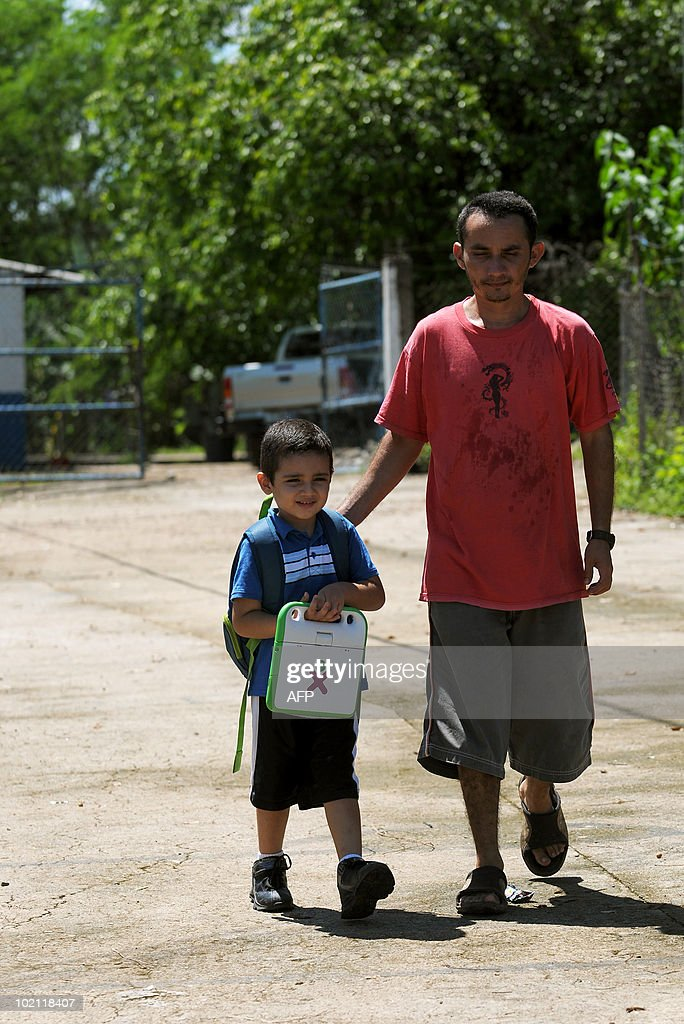 STORY by OSCAR BATRES - Antonio Ramirez (L) carries his OLPC XO laptop as he walks out from school with his father Rafael Ramirez (R), in the town of Nombre de Jesus, 90km north from San Salvador on June 14, 2010. The Salvadorean Ministry of Education launched the 'Closing the gap of knowledge' project aimed at improving educational processes with technology, for students in very poor agricultural areas of El Salvador. AFP PHOTO/Jose CABEZAS