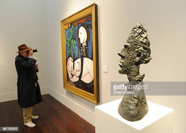 ART by PAOLA MESSANA A man photographs Pablo Picasso's 'Nude Green Leaves and Bust' estimated at USD 70 million to 90 million next to Alberto...