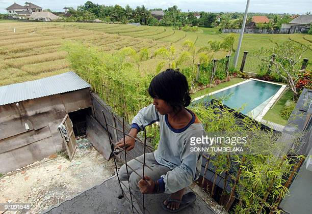 WITH 'INDONESIABALITOURISMENVIRONMENT' by Presi Mandari Balinese worker constructs a villa next to a newly built residence with swimming pool beside...