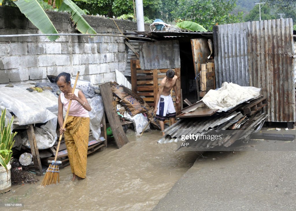 STORY 'ETIMOR-POVERTY-ECONOMY' by Raimundos Oki This picture taken on January 2, 2013 shows an East Timorese family cleaning their hut in Dili which flooded during heavy rain. The tiny half-island nation of East Timor is struggling with widespread poverty and a laggard economy, despite offshore energy reserves worth billions of dollars and a steady stream of aid into Asia's youngest nation. AFP PHOTO / Valentino DE