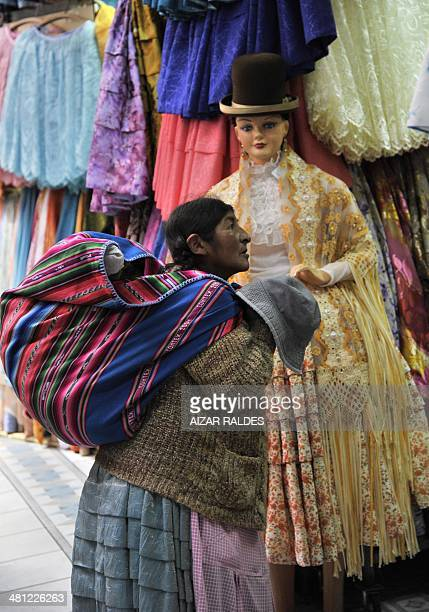 STORY by Raul Burgoa An Aymara woman visits a shopping arcade which only sells Bolivian typical costumes in La Paz on March 14 2014 AFP PHOTO / AIZAR...