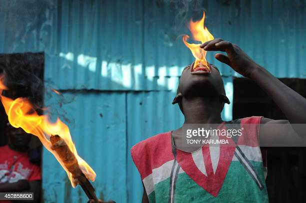 STORY by Reuben KYAMA Thomas MORFIN A member of a youth corps campaigning for peace performs an act at the sprawling Kibera slum in Nairobi on July...