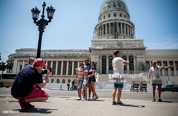 STORY by Rigoberto Diaz Tourists from the United States pose in front of the Capitol in Havana on April 6 2015 With sanctions easing Cuba is bracing...