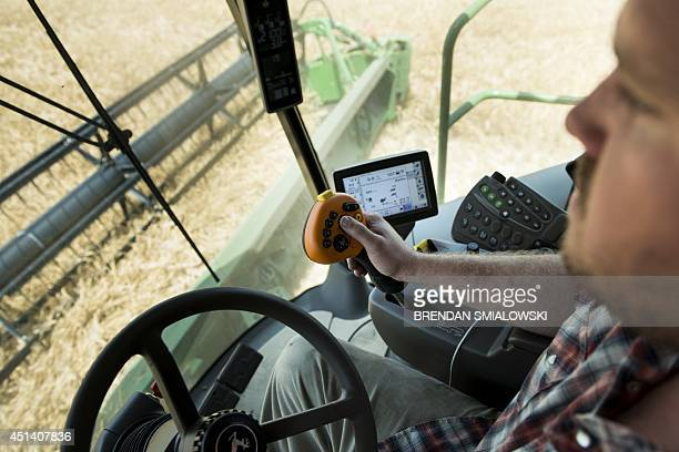 STOY by Rob LEVER USfarmITInternetenvironment Dale Blessing controls his combine harvester while harvesting barley on June 17 2014 in Milford...