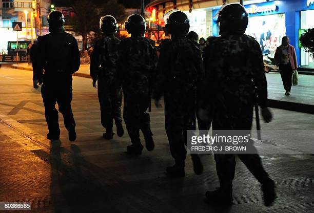 RELIGION by Robert Saiget Paramilitary forces in riot gear patrol the streets of old Lijiang on March 24 2008 in southwest China's Yunnan provinceThe...