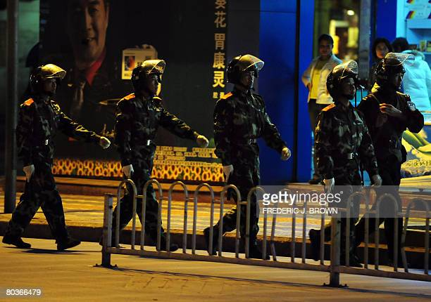 RELIGION by Robert Saiget Shopkeepers watch as Chinese paramilitary forces march on patrol through the streets of Lijiang on March 24 2008 in...