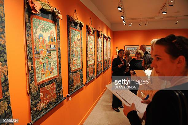 STORY by Sebastian Smith LifestyleUSartauction Journalists view a set of seven thangkas of the Great Fifth Dali Lama and his lineage from Tibet circa...