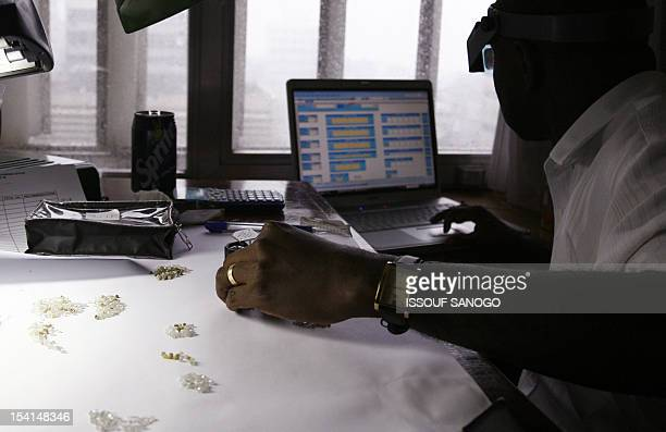 STORY by Susan Njanji A man checks raw diamonds 10 August 2007 at Gold and Diamond department Sierra Leone Central Bank in Freetown As it pieces...