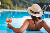 Rear view of a woman, wearing summer hat, sitting in a pool, drinking cocktails from a glassmade glass with a drinking straw, life in the summer, happy hour, private pool in a luxury house, wealth and