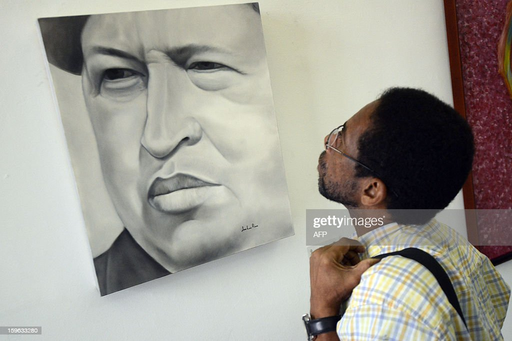 STORY by Valeria Pacheco A man visits the exhibition on Venezuelan President Hugo Chavez titled 'Chavez Vive y Vencera' (Chavez Lives and Will Overcome), in Caracas on January 17, 2013. Chavez remains gravely ill in a Havana hospital some five weeks after complications arose during his fourth round of cancer surgery. AFP PHOTO/Leo RAMIREZ