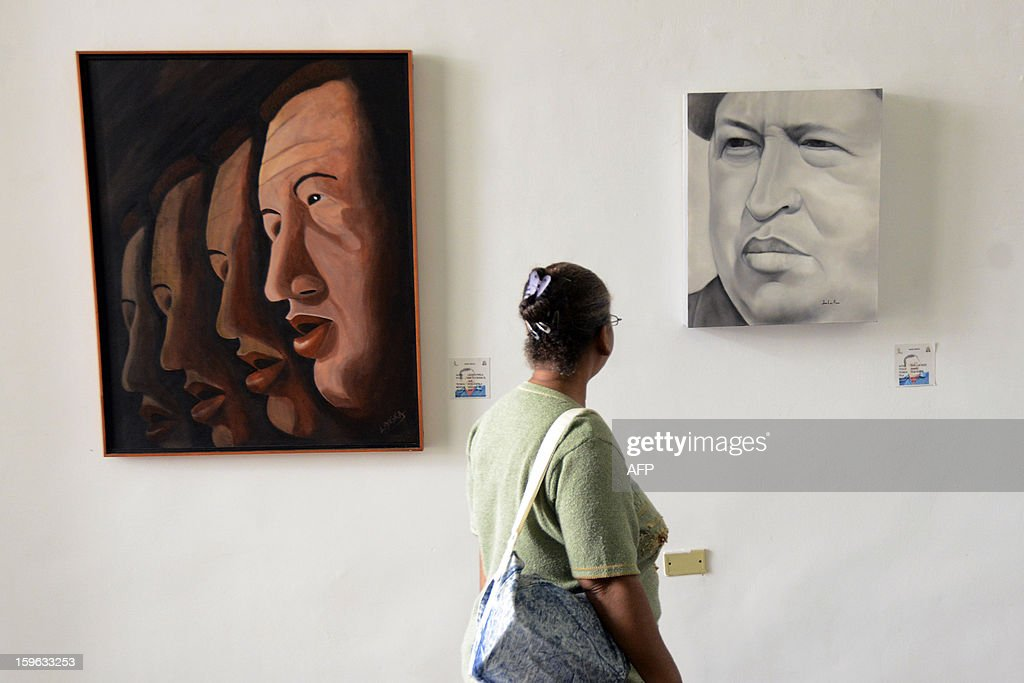 STORY by Valeria Pacheco A woman visits the exhibition on Venezuelan President Hugo Chavez titled 'Chavez Vive y Vencera' (Chavez Lives and Will Overcome), in Caracas on January 17, 2013. Chavez remains gravely ill in a Havana hospital some five weeks after complications arose during his fourth round of cancer surgery. AFP PHOTO/Leo RAMIREZ