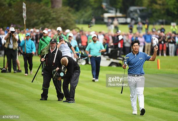 ByeongHun An of South Korea acknowledges the crowd as he walks towards the 18th green during day 4 of the BMW PGA Championship at Wentworth on May 24...