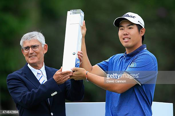 ByeongHun An of South Korea poses with the trophy and David Williams Chairman of The European Tour following his victory during day 4 of the BMW PGA...