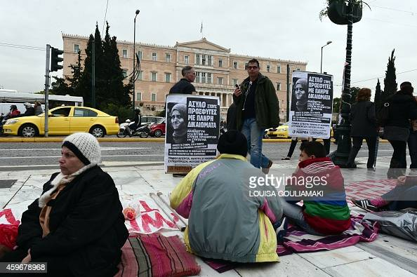 Bypassers look at Syrian refugees who are on on the fifth day of their hunger strike at central Syntagma square in Athens on November 28 2014 The...