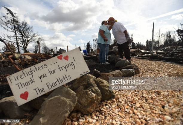 TOPSHOT Byron and Joanne Bartlett pose for a photo in front of a sign they made for firefighters at as they search for remains at their burned...