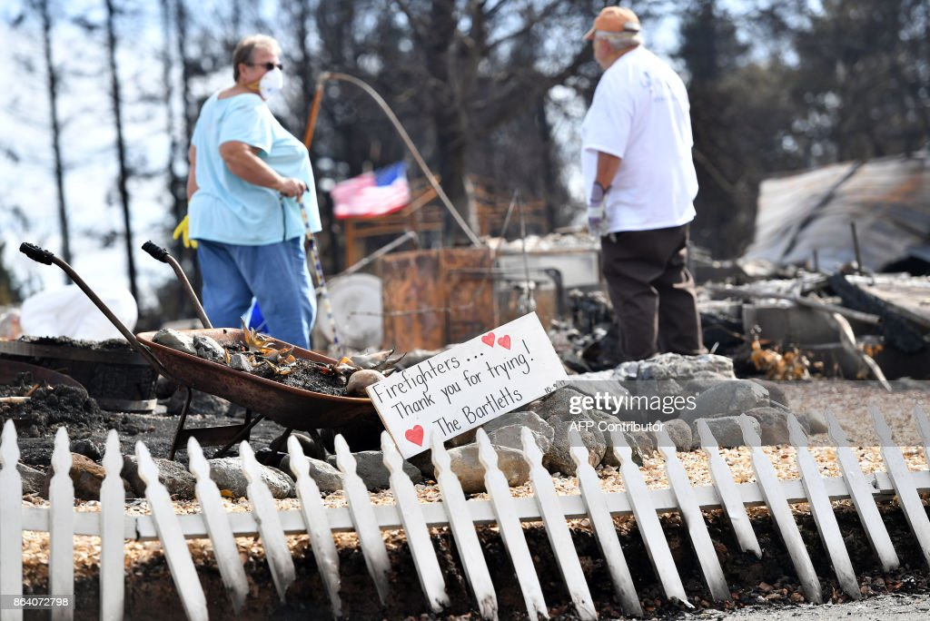 Byron (R) and Joanne Bartlett (L) search for remains at their burned residence in the Coffey Park area of Santa Rosa, California on October 20, 2017. Residents are being allowed to return to their burned homes on October 20 to grieve and search through remains. Around 5,700 homes and businesses have been destroyed by the fires, the deadliest in California's history. /