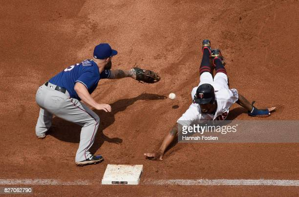 Byron Buxton of the Minnesota Twins dives back safely to first base as the ball gets past Mike Napoli of the Texas Rangers during the fourth inning...