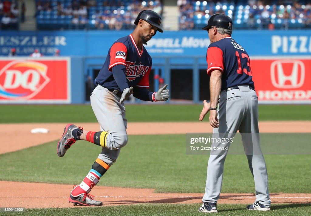 Byron Buxton #25 of the Minnesota Twins is congratulated by third base coach Gene Glynn #13 after hitting his third home run of the game a solo home run in the ninth inning during MLB game action against the Toronto Blue Jays at Rogers Centre on August 27, 2017 in Toronto, Canada.