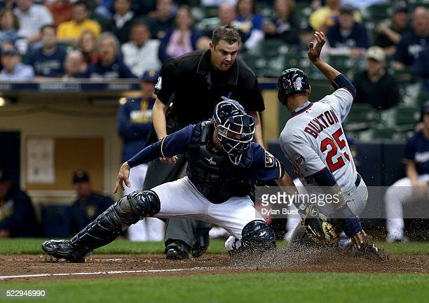 Byron Buxton of the Minnesota Twins slides safely into home past Jonathan Lucroy of the Milwaukee Brewers in the eighth inning at Miller Park on...