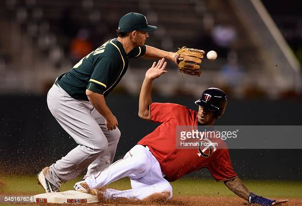 Byron Buxton of the Minnesota Twins slides safely into third base as Danny Valencia of the Oakland Athletics fields the ball during the sixth inning...