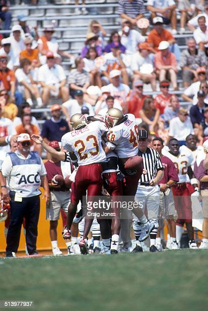 Byron Capers and Todd Rebol of the Florida State Seminoles celebrate with a teammate during an NCAA game against the Clemson Tigers on September 9...