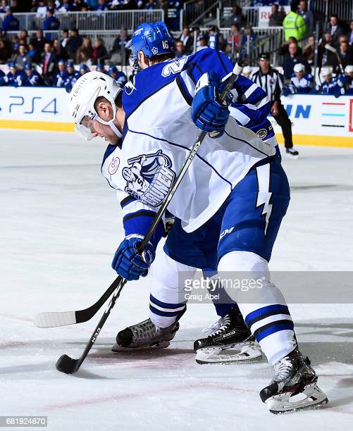Byron Froese of the Syracuse Crunch takes a face off with Brett Findlay of the Toronto Marlies during game 3 action in the Division Final of the...