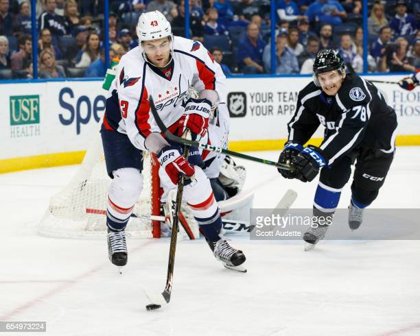 Byron Froese of the Tampa Bay Lightning skates against Tom Wilson of the Washington Capitals during the third period at Amalie Arena on March 18 2017...
