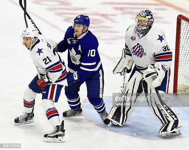 Byron Froese of the Toronto Marlies fights for crease space with Tyson Fawcett and Linus Ullmark of the Rochester Americans during AHL Game action on...