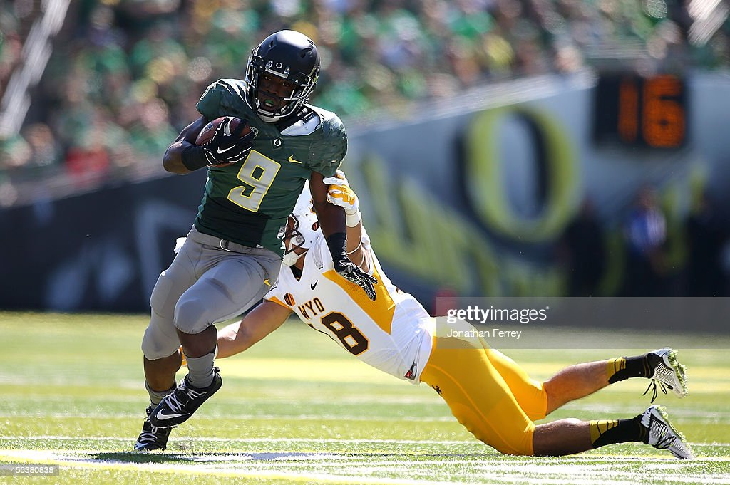 Byron Marshall of the Oregon Ducks breaks a tackle by Xavier Lewis of the Wyoming Coyboys to run for a touchdown at Autzen Stadium on September 13...