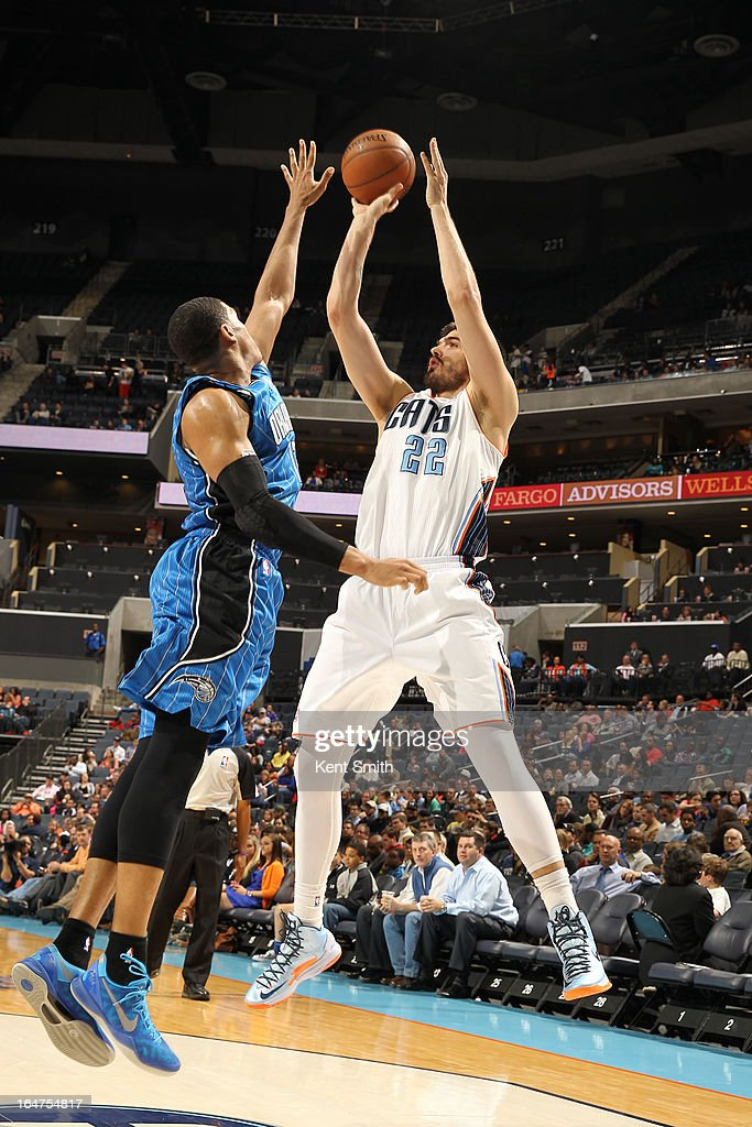 Byron Mullens of the Charlotte Bobcats shoots against Tobias Harris of the Orlando Magic at the Time Warner Cable Arena on March 27 2013 in Charlotte...