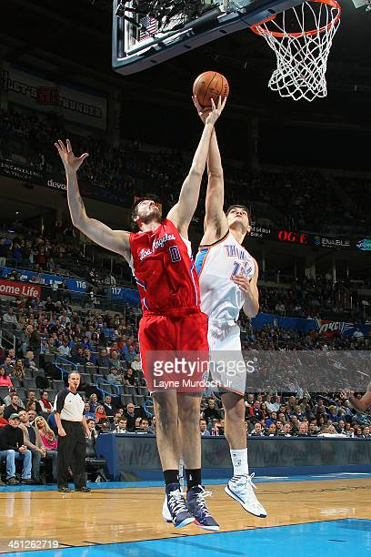 Byron Mullens of the Los Angeles Clippers goes up for a rebound against Steven Adams of the Oklahoma City Thunder on November 21 2013 at the...