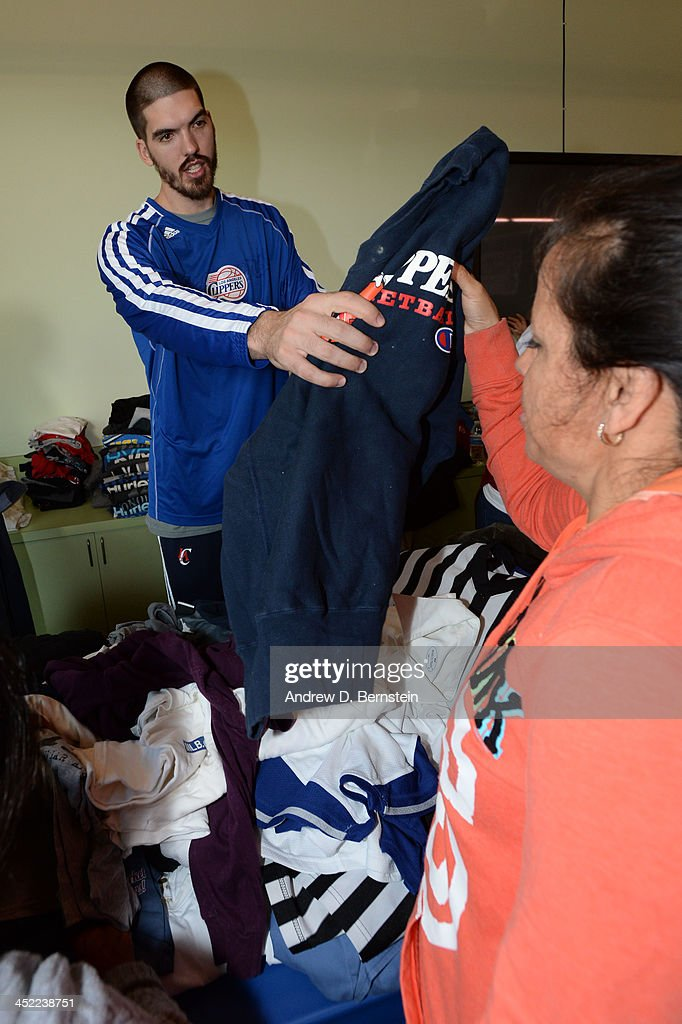 Byron Mullens of the Los Angeles Clippers hands out shirts during the Teamwork at the Table Event at the St Joseph Center on November 26 2013 in...