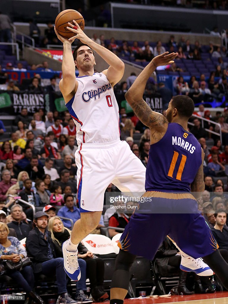 Byron Mullens of the Los Angeles Clippers shoots over markieff Morris of the Phoenix Suns at Staples Center on December 30 2013 in Los Angeles...
