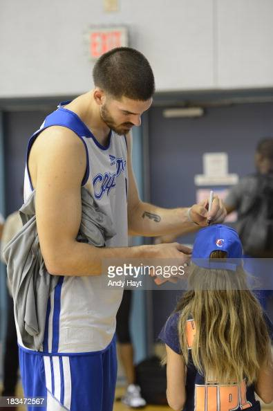 Byron Mullens of the Los Angeles Clippers signs a hat for a young fan in training camp at RIMAC Arena on October 4 2013 in La Jolla California NOTE...