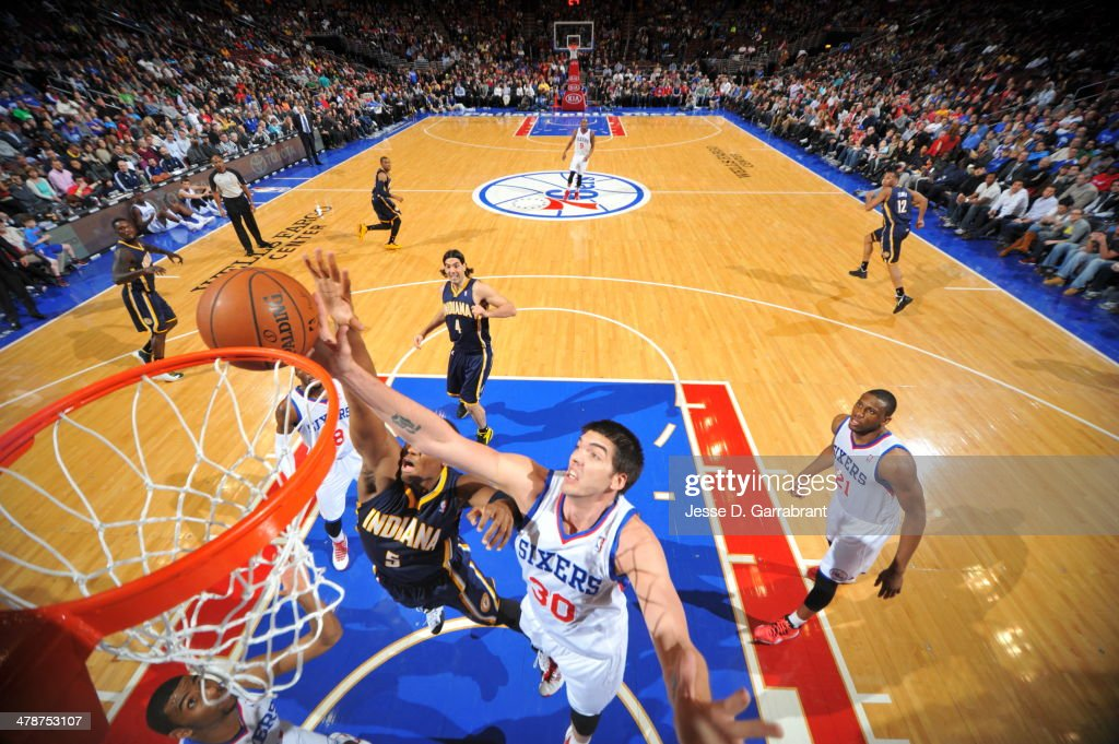 Byron Mullens of the Philadelphia 76ers rebounds against the Indiana Pacers at the Wells Fargo Center on March 14 2014 in Philadelphia Pennsylvania...