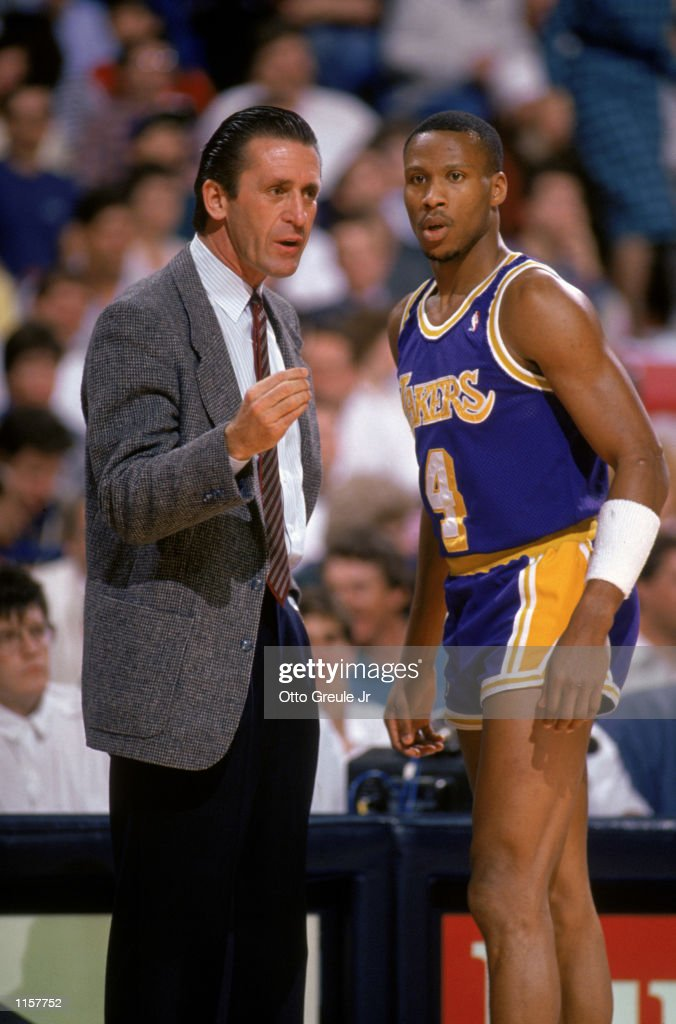 Byron Scott of the Los Angeles Lakers listens to head coach Pat Riley during an NBA game against the Sacramento Kings at Arco Arena in Sacramento...